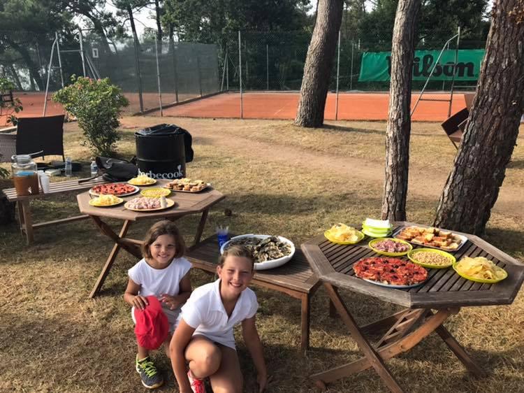 Près d'un court de tennis, préparation d'un barbecue.