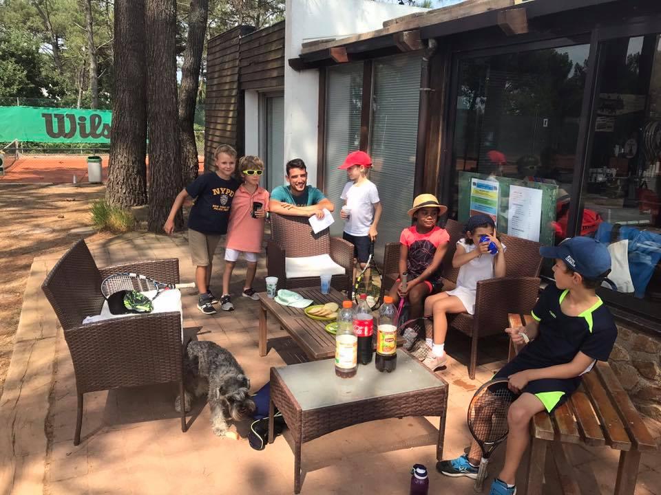 Des enfants joueurs de tennis prennent un goûter sur la terrasse du Tennis Club de Quehan.