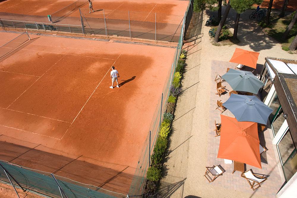 Joueur de tennis sur court en terre battue.
